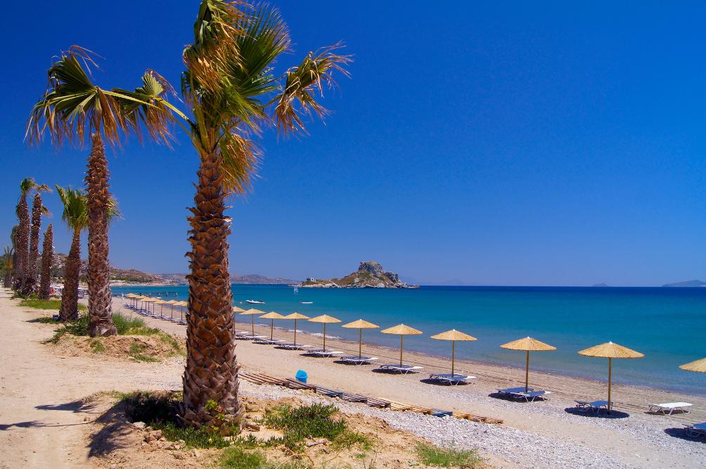 Strand in der Kefalos Bucht mit Palmen, Liegen und Sonnenschirmen